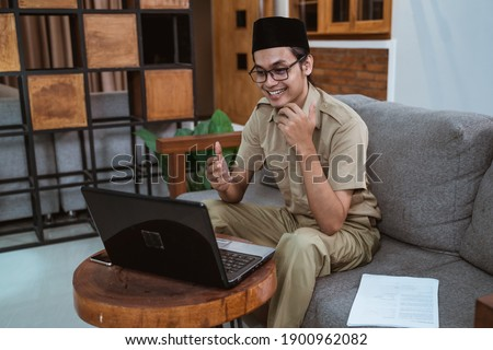male teacher in civil servant uniform with hand gestures during online meeting using a laptop computer when working from home