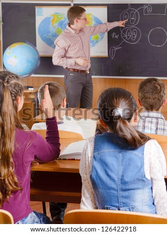Male teacher in front of elementary age schoolchildren.