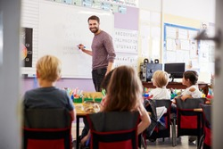 Male Teacher Standing At Whiteboard Teaching Maths Lesson To Elementary Pupils In School Classroom