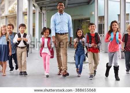 Male teacher walking in corridor with elementary school kids