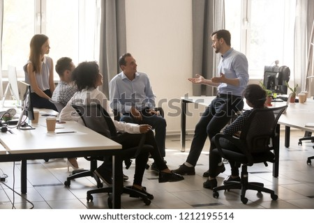 Male team leader boss talking to diverse business people at office meeting, multiracial employees group listening to ceo mentor coach speaking explaining new idea at corporate training or briefing