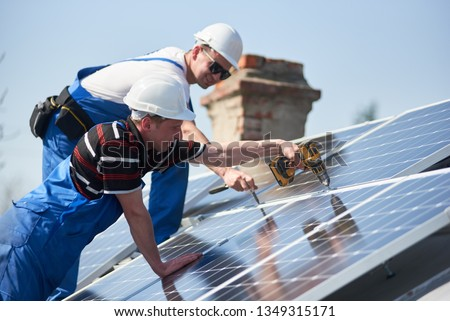 Male team workers installing stand-alone solar photovoltaic panel system using screwdriver. Electricians mounting blue solar module on roof of modern house. Alternative energy sustainable concept