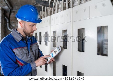 Male Technician Doing Meter Reading Using Tablet stock photo