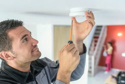 Male technician is fitting a fire alarm in the ceiling