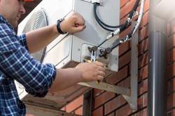 Male technician repairing outdoor air conditioner unit