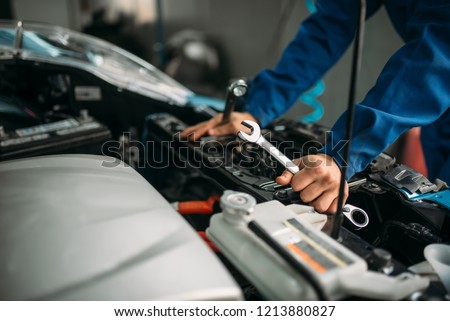 Male technician works with car engine #1213880827