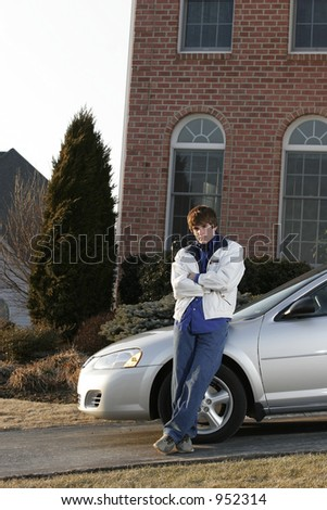 male teen youth leaning on new car in driveway of upscale home