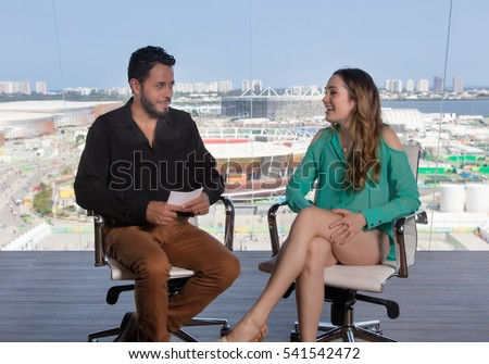 Male television presenter asking a famous female celebrity at modern tv studio