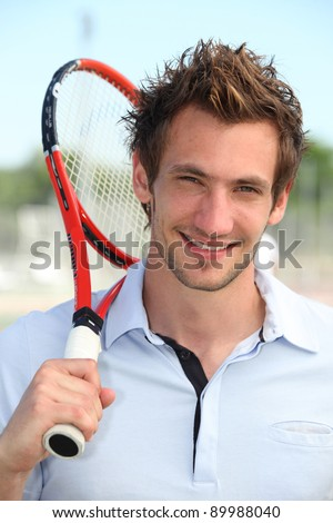 Male tennis player holding racquet over shoulder