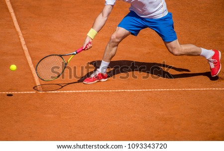 Male tennis player in action on the court on a sunny day