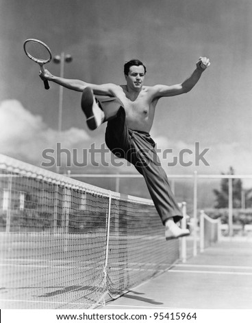 male tennis player jumping over ...
