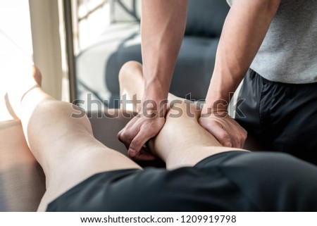 Male therapist giving leg and calf massage to athlete patient on the bed in clinic, sports physical therapy concept