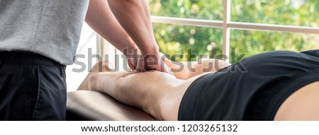 Male therapist giving leg massage to athlete patient on the bed in clinic for sports physical therapy concept, banner proportion
