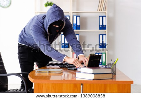 Male thief in balaclava in the office  #1389008858