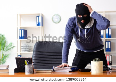 Male thief in balaclava in the office  #1389008864