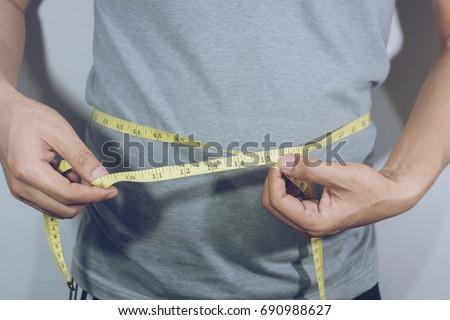 Male torso with measure tape on waistline .selective focus Сток-фото ©