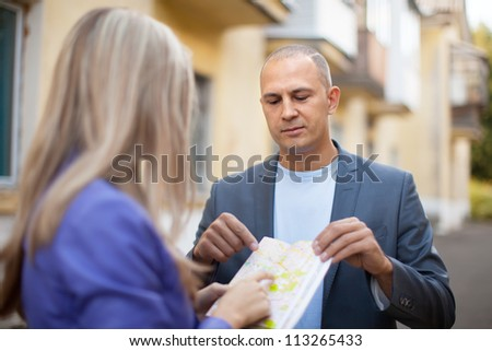 Male tourist asks for directions from a woman