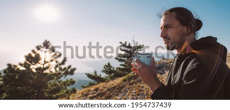 Male tourist drinks tea on the top of the mountain at sunrise. Young handsome guy with tourist equipment joyfully meets the morning sun in the mountains with a mug of hot tea or coffee