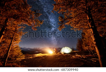Male tourist enjoying in his camp near the forest at night. Man sitting near campfire and tent under beautiful night sky full of stars and milky way. Long exposure #687309940