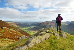 Male tourist enjoying sunset view of Great Langdale valley in the Lake District, famous for its glacial ribbon lakes and rugged mountains. Popular vacation destination in Cumbria, North West England.