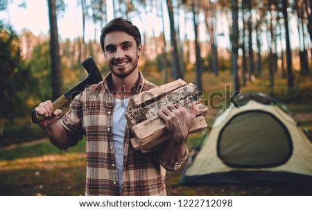 Male tourist exploring new places. Handsome bearded man on nature. Man with ax and firewood near touristic tent. Lumberjack #1222712098