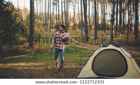 Male tourist exploring new places. Handsome bearded man on nature. Man with ax and firewood near touristic tent. Lumberjack