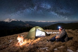 Male tourist have a rest in his camp at night. Guy with a headlamp sitting near campfire and tent under beautiful sky full of stars and milky way. On the background snow-covered mountains