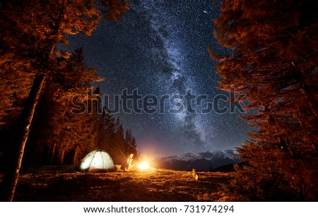 Male tourist have a rest in his camp near the forest at night. Man sitting near campfire and tent under beautiful night sky full of stars and milky way. Long exposure #731974294