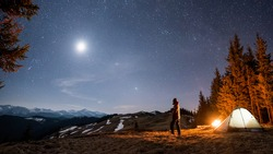 Male tourist have a rest in his camp near the forest at night. Man standing near campfire and tent under beautiful night sky full of stars and the moon, and enjoying night scene. Aspect ratio 16:9
