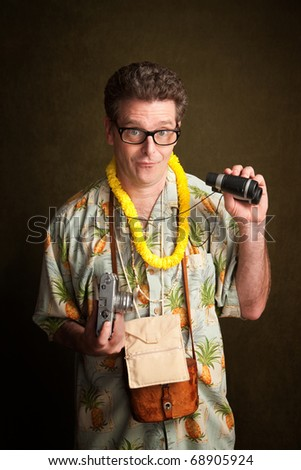 Male tourist in a tropical island outfit holding a camera and binoculars