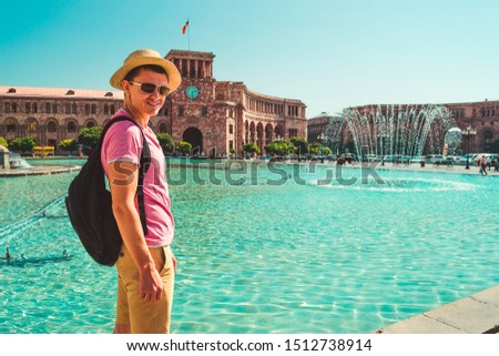 Male tourist in hat with backpack on central square of Yerevan. Caucasian adult man alone explore Armenia. Touristic architecture landmark. Sightseeing city tour. Travel and armenian tourism concept.
