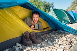 Male tourist meets good sunny morning, sitting in touristic tent with cup of hot tea. Active vacation concept image