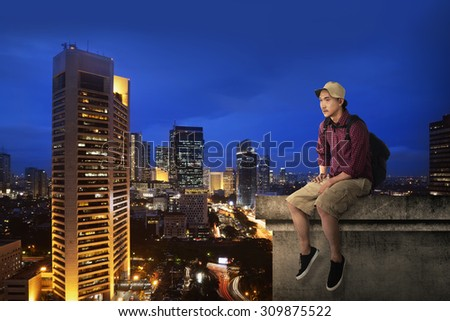 Male tourist sitting on the building rooftop at night time