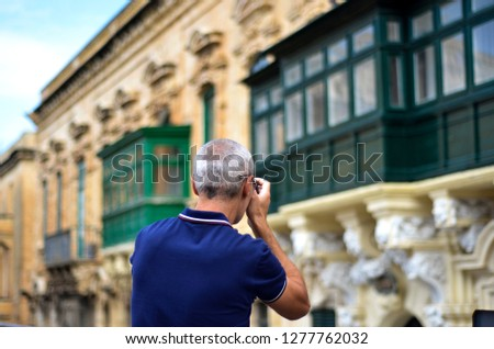 Male tourist taking photos of traditional Maltese balconies in the city center of the old town of Valetta, Malta