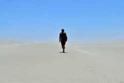 Male tourist wandering through the sand dunes of Farewell Spit in New Zealand