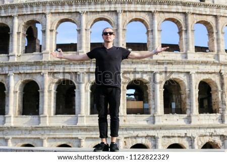 Male tourist wearing black clothes and standing near Coloseum in background in Rome, Italy. Concept of traveling and last minute cheap tours to ancient Europe, landmarks and tourists. #1122822329