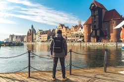 Male tourist with a backpack in sunny winter weather walks sightseeing in the old town of Gdansk in Poland on Motlawa river embankment against Gdansk Crane or Brama Zuraw.