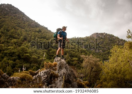 male tourist with trekking poles and backpack stands on hill against background of mountains of Turkey