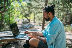 Male tourist working on a laptop outdoors in a camping. Young guy, freelancer working online at a laptop computer on a hike in the mountains outdoors. The ability to work from anywhere in the world.