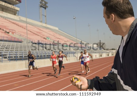 Male trainer measuring time while athletes racing