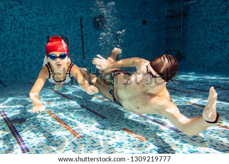 Male trainer with a little girl in the pool teaches to swim under water #1309219777