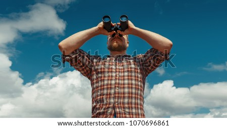 Male Traveler Looking Through Binoculars In The Distance Against The Sky. Low Angle Point Shoot with copy-space