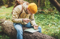 Male traveler sat down on a log in the woods, holding a map and looking for direction navigation, search path or road.