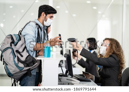 Male traveler shows phone to female officer at airline check in counter for issue airplane ticket boarding pass. Woman staff wear face mask to prevent from coronavirus pandemic. New normal lifestyle Foto stock ©