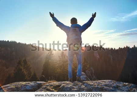 Male traveler standing on the cliff against wooded hills and cloudy sky at sunrise. Man stands hands up, greeting the sun. Adult tourist with backpack looking to misty hilly valley below. Location #1392722096