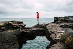 Male traveler standing on the rocks at seaside and looking a nature scene in background. Wanderlust people enjoying amazing outdoor landscape view in Iceland. One guy in red jacket watching the ocean.