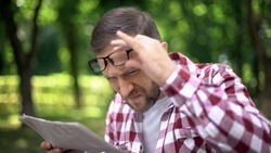 Male trying to read newspaper in park, poor sight, farsightedness, myopia