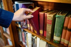 Male university student hand choosing and picking vintage book from old wooden bookshelf in college library. Antique textbook resources for education research. History, Law and Literature learning