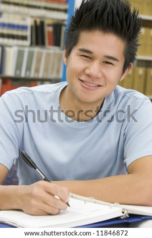 Male university student writing report in library