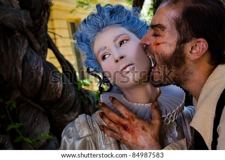 Male vampire with wounds biting young woman in medieval dress